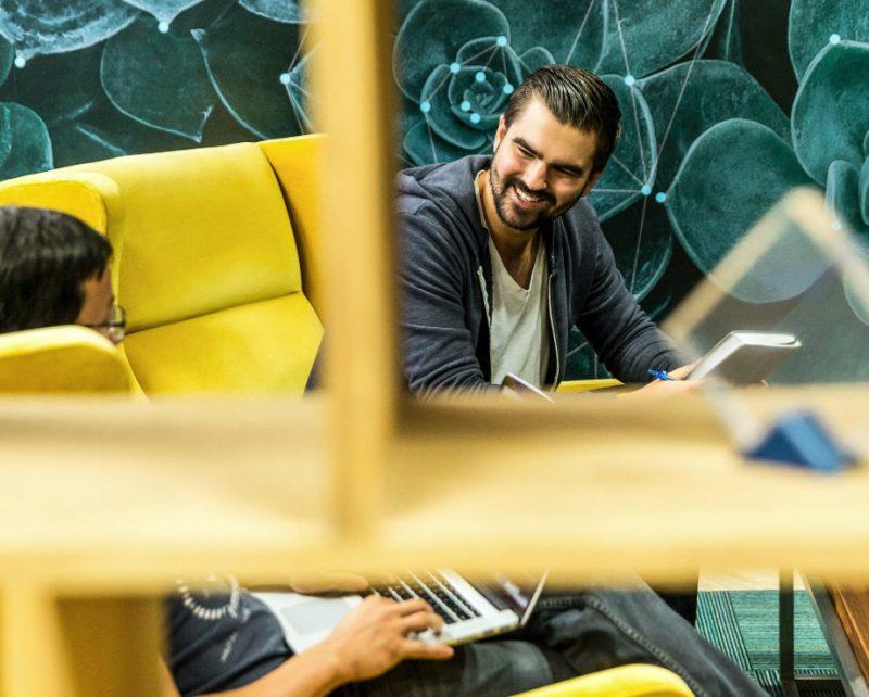 Männer arbeiten und unterhalten sich in Lounge