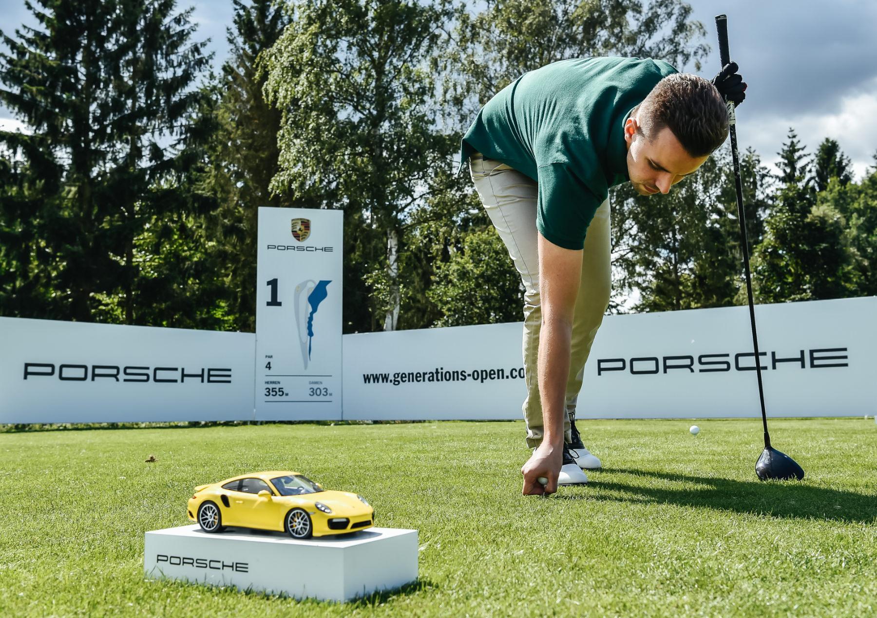 Porsche Generationsopen Golfer mit Ball und Miniporsche