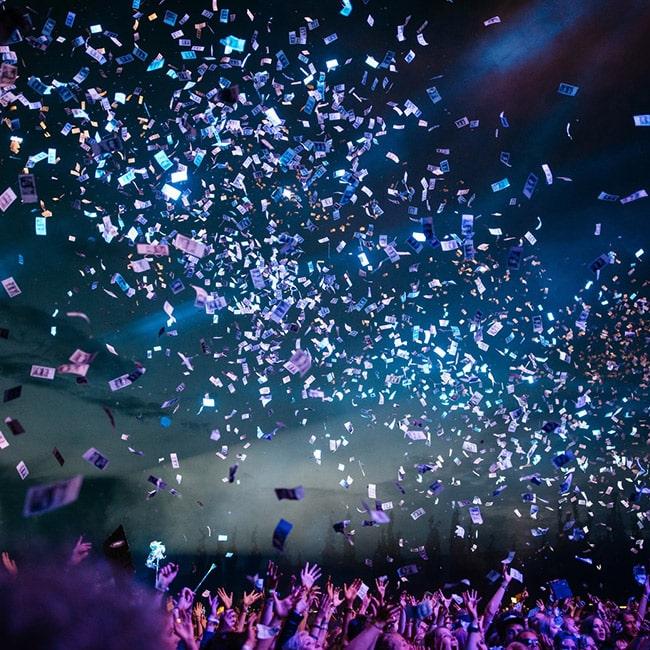 Gelscheine fliegen bei einem Event über einer jubelnden Menge.