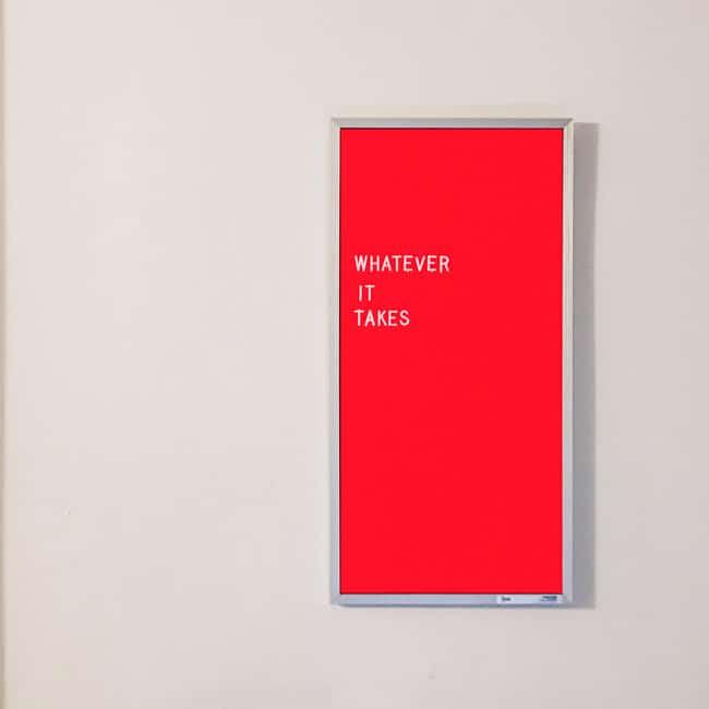 """Eine rote Pinwand mit weißen Buchstaben. Die Worte darauf. """"Whatever it takes"""". Mit dieser Einstellung steht follow red an Ihrer Seite."""