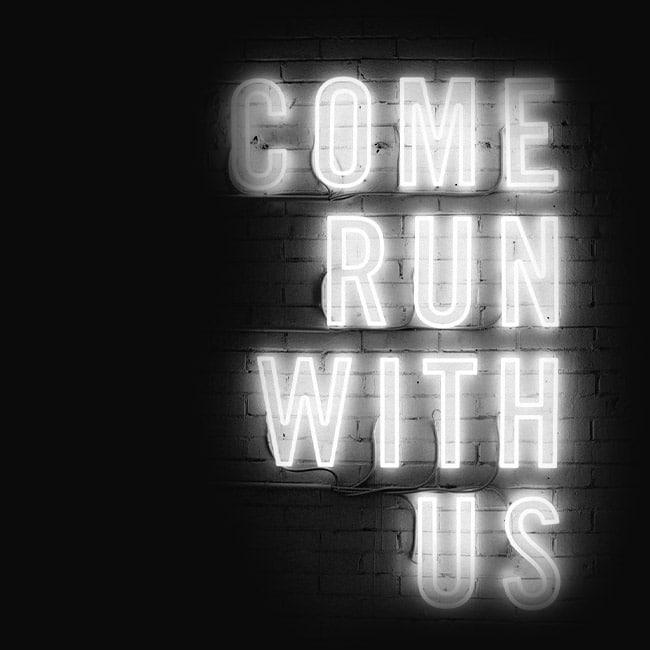 """Eine Leuchtreklame mit den Worten """"Come run with us"""". Das nehmen wir wörtlich und erreichen mit unseren Roadshows Menschen auf der ganzen Welt."""