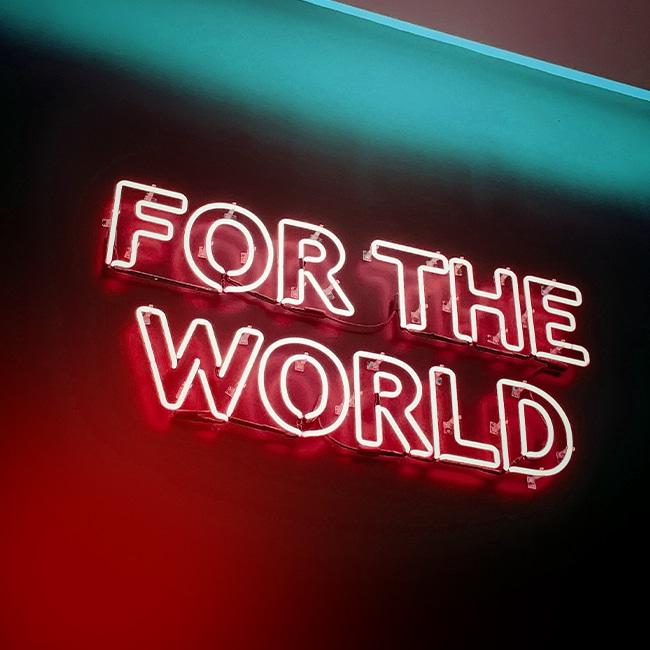 """Eine Leuchtreklame mit den Worten """"For the World"""". follow red kommuniziert global und schafft als PR-Agentur Reichweite."""