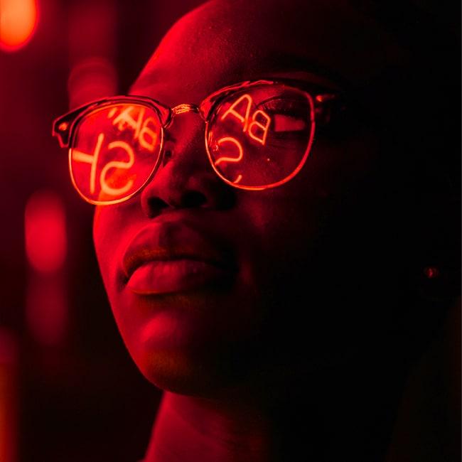 Ein Mann mit Sonnenbrille schaut gebannt auf eine rote Leuchtreklame, die für Digital Experiences steht.
