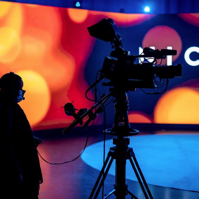 Eine Kamera filmt im Studio. Beim Hybrid Event kann entweder live übertragen oder bereits vorproduziert werden.