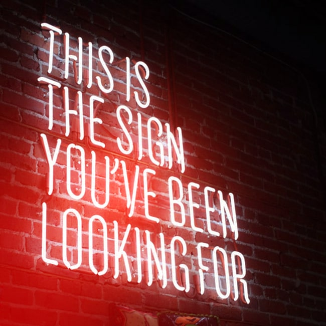 "Eine Leuchtreklame mit den Worten: ""This is the Sign you have been looking for"". Follow red ist die Agentur, nach der Sie gesucht haben."